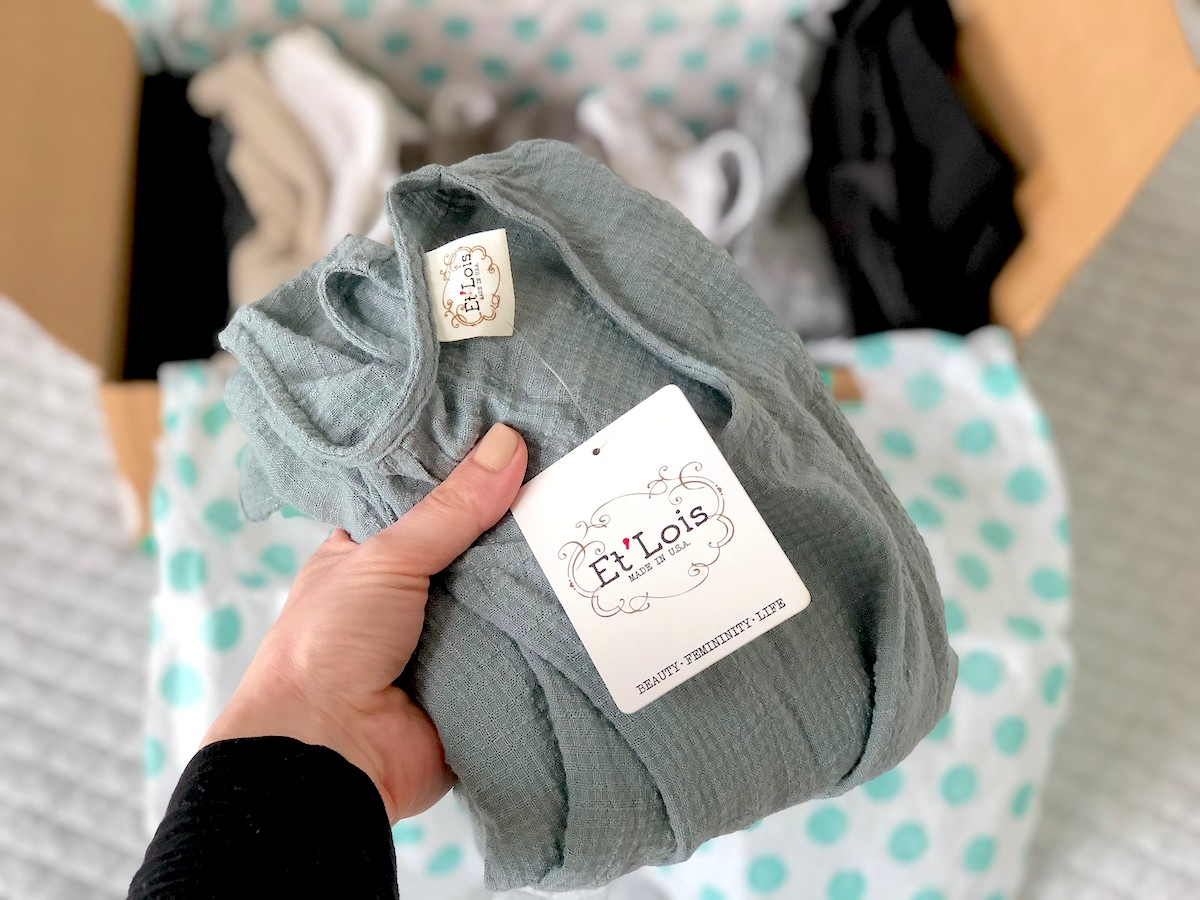 hand holding a blue green piece of clothing with tag
