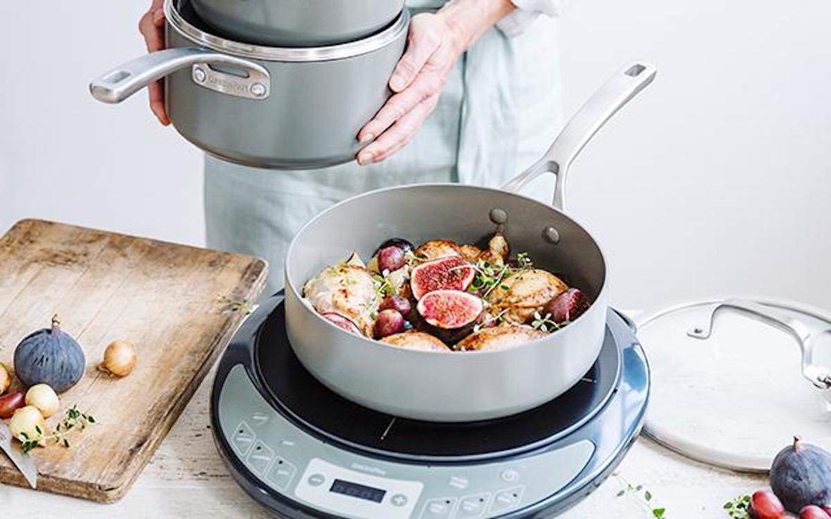 person holding pot next to saucepan with food sitting on burner