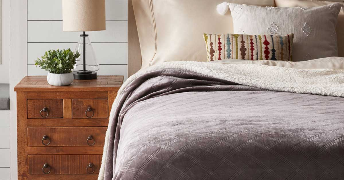 gray sherpa blanket on a bed in a bedroom