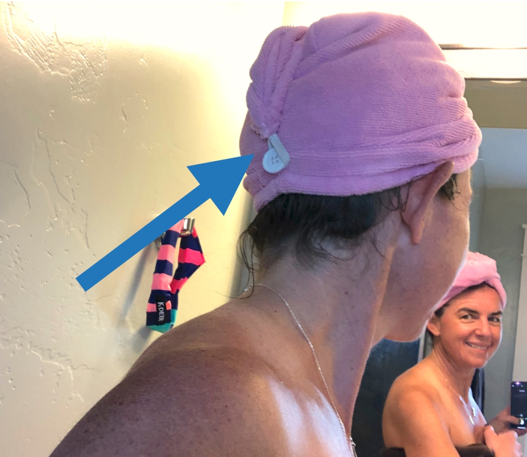 woman wearing pink hair towel looking in mirror smiling
