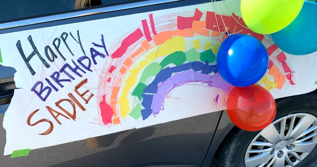 birthday sign on side of car with rainbow