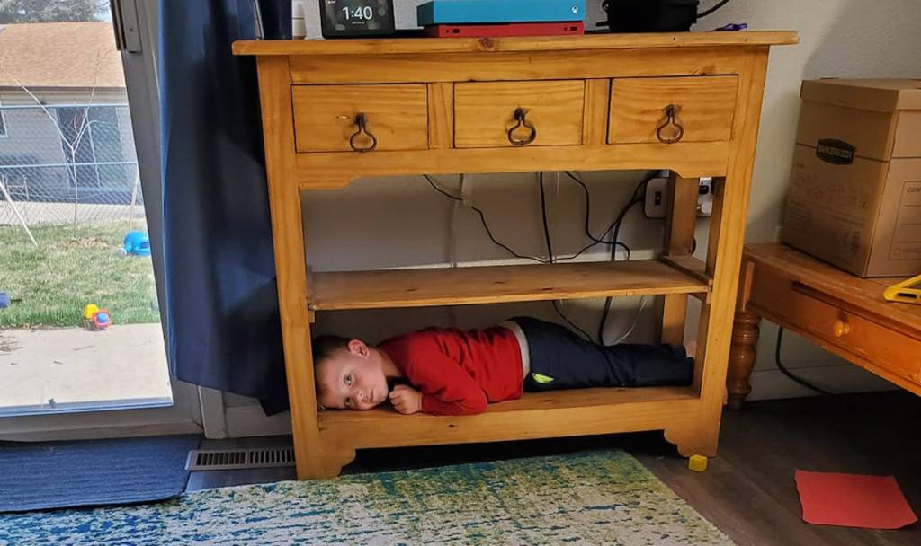 child hiding under wood console table