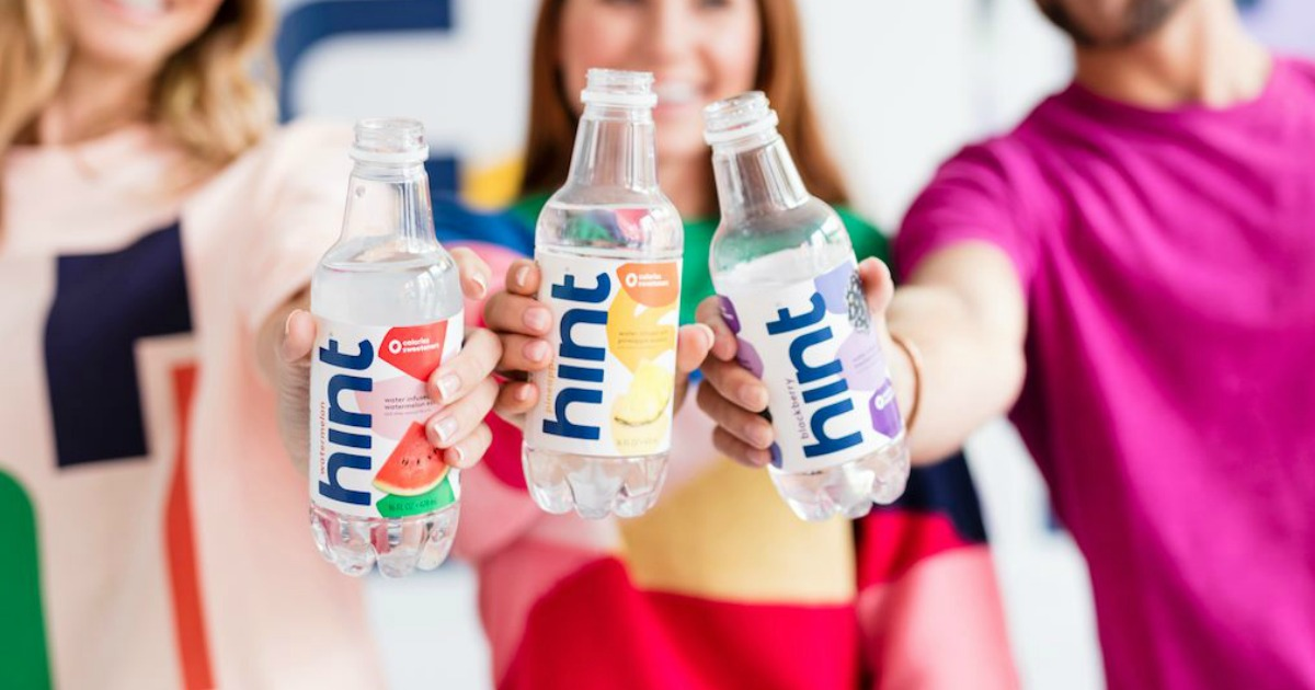 three people holding up hint water bottles