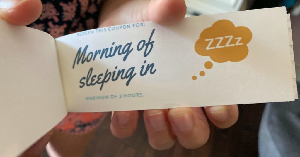holding Mother's Day coupon book with morning of sleeping in coupon