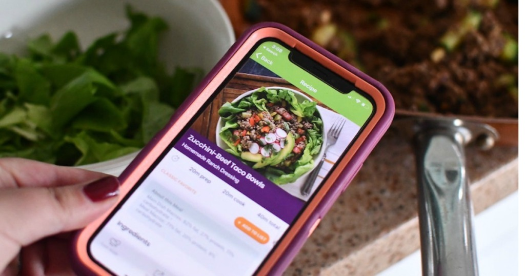 holding iphone with eMeals recipe on screen