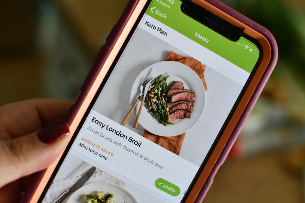 holding iPhone with eMeals Keto plan on screen