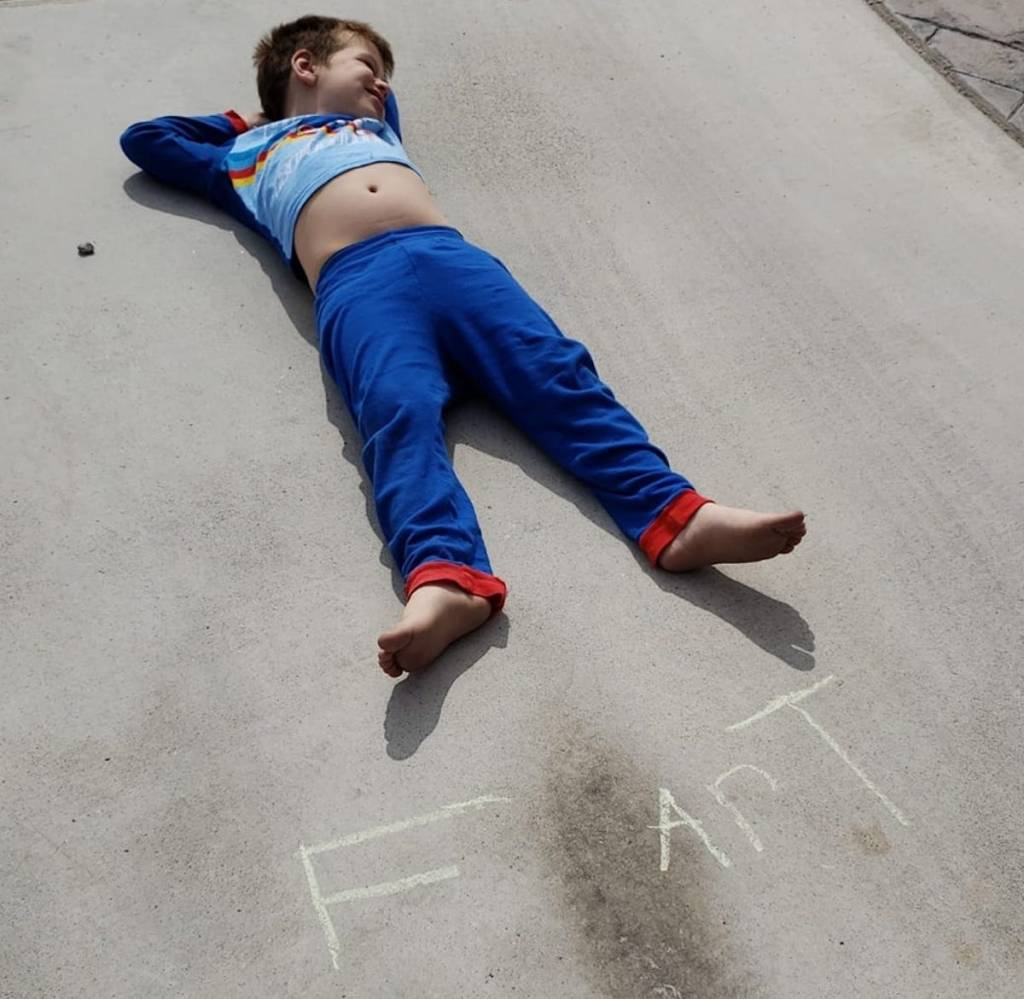 boy laying on cement driveway with chalk word fart on ground with hashtag home schooling