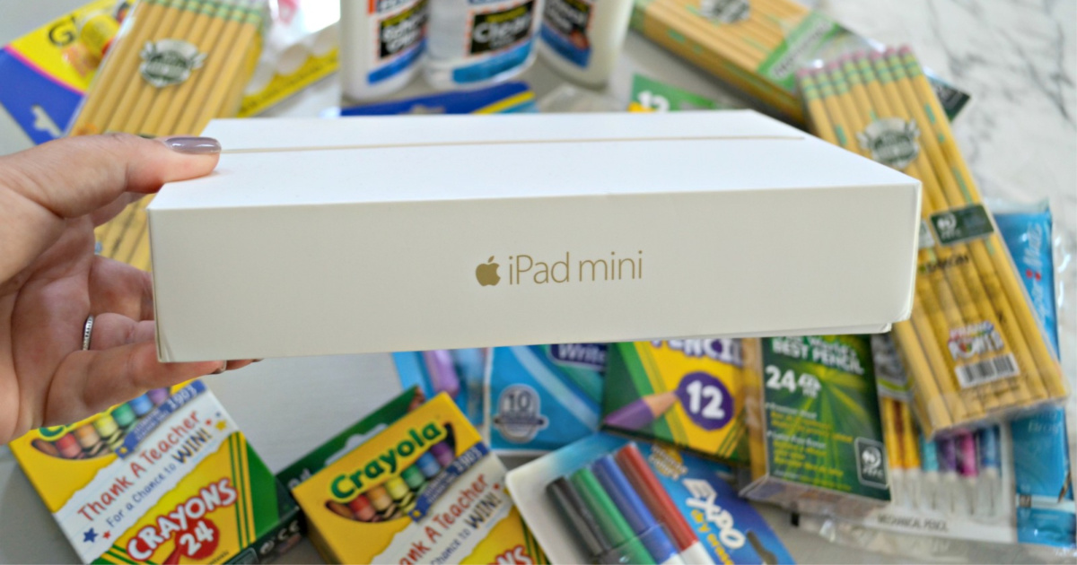 ipad mini box being held up in front of multiple school supplies such as crayola crayons, pencils, markers and more