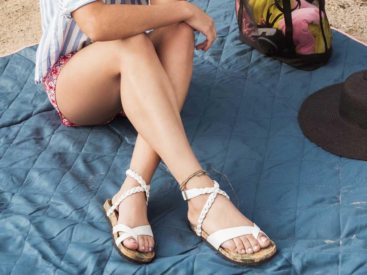 woman wearing white muk luk sandals sitting on a blue blanket