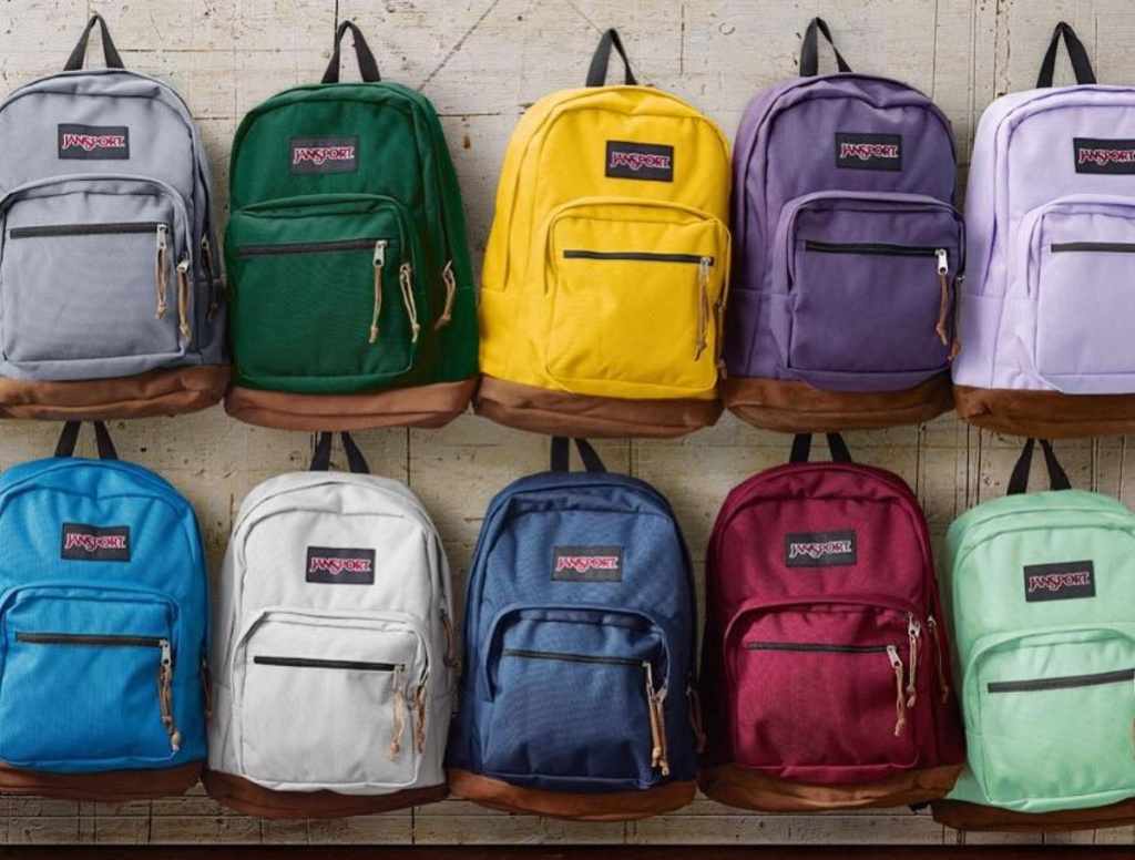 Jansport backpacks hanging on a wall
