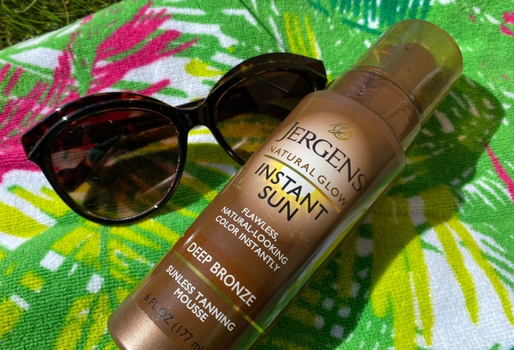 bottle of jergens self tanner and sunglasses laying on green beach towel