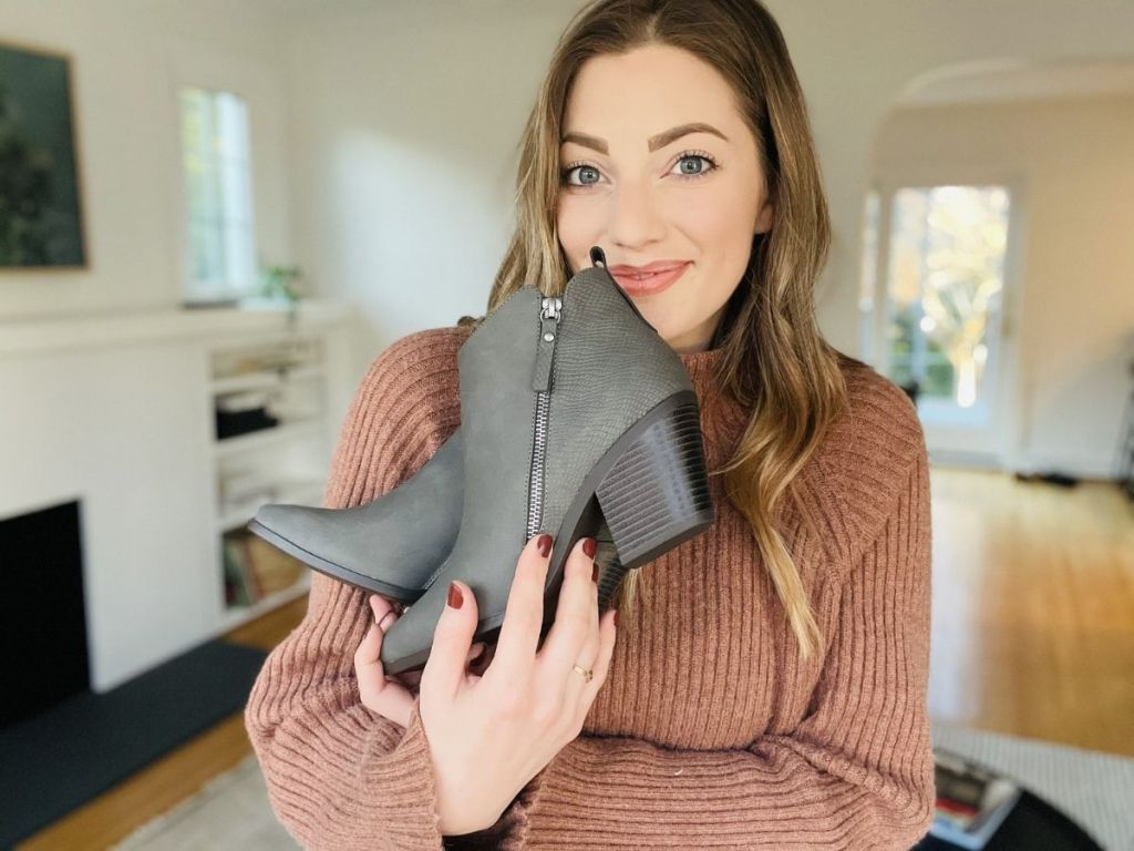 woman holding gray booties in her arms