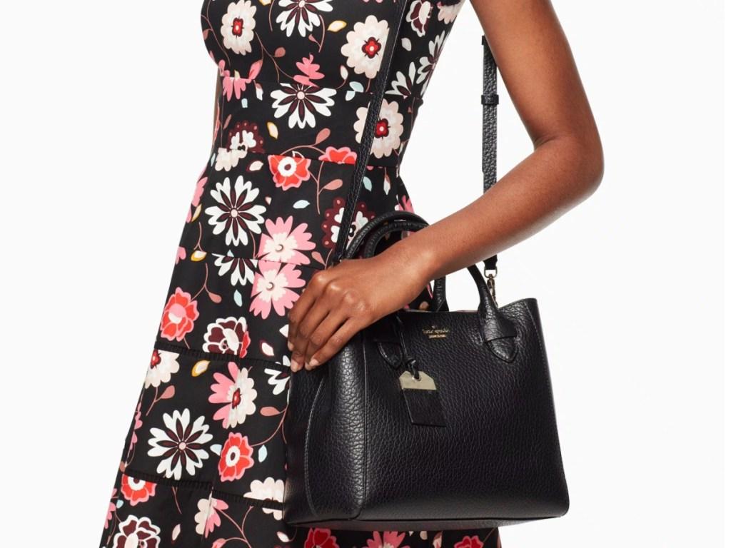 woman in flower dress carrying black bag