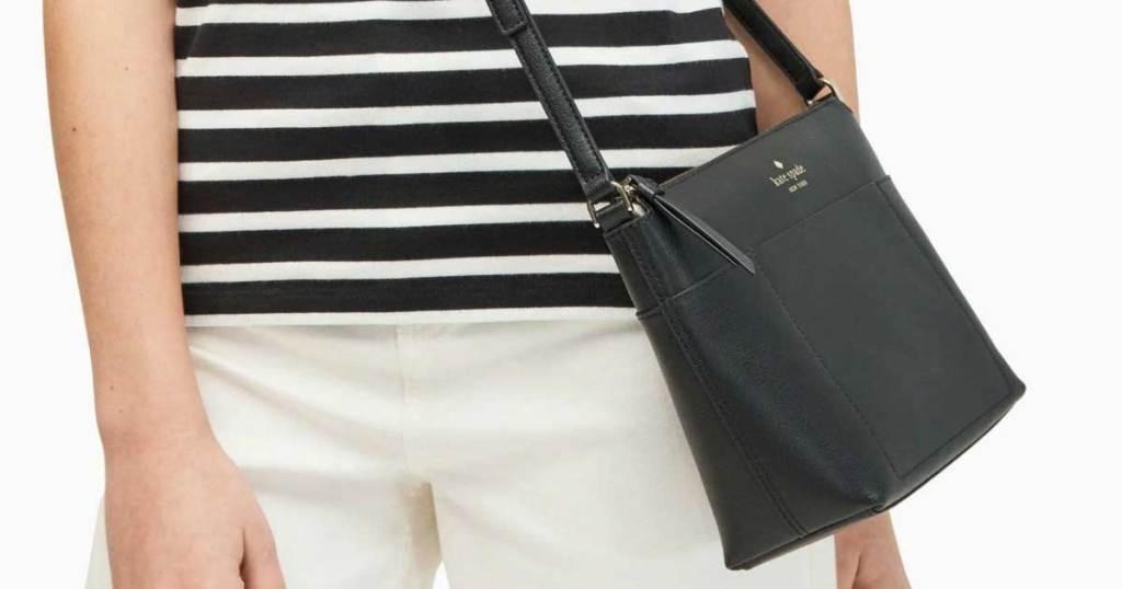 woman wearing a kate spade black crossbody purse on her hip