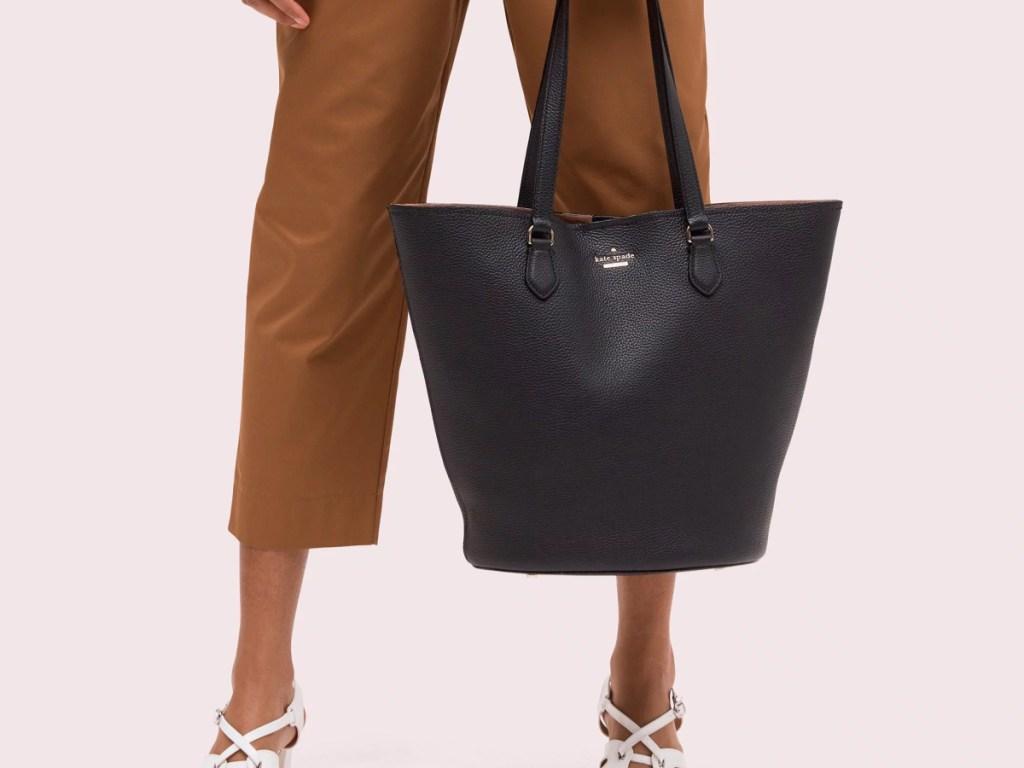 woman in brown pants holding black kate spade bag