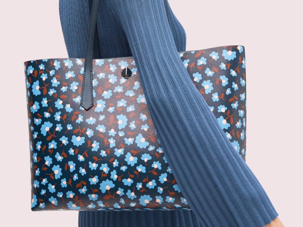 woman in blue sweater holding flowered bag