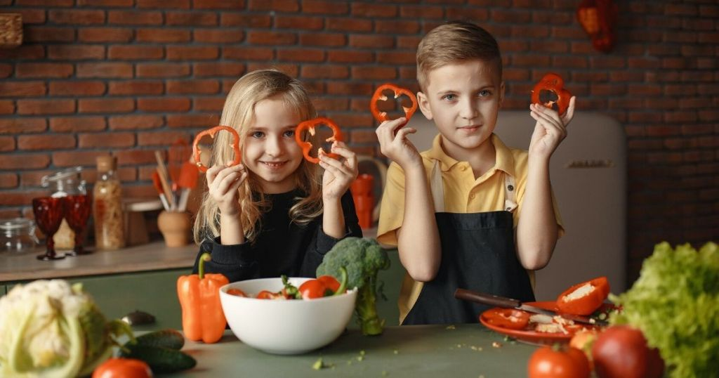 two kids holding up peppers to cook