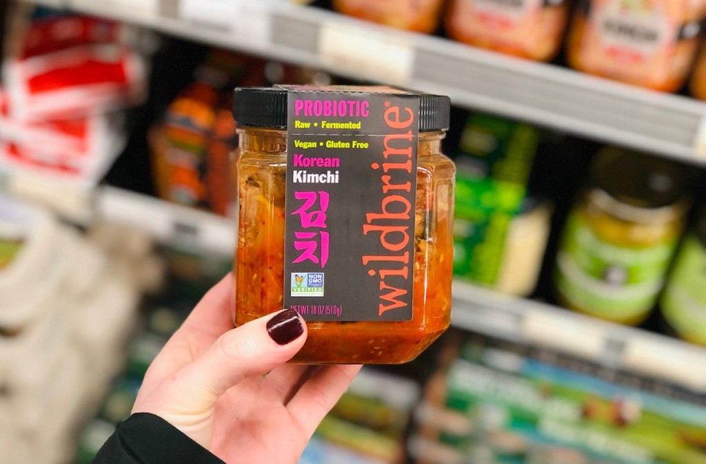 hand holding a glass jar of kimchi in store fridge aisle