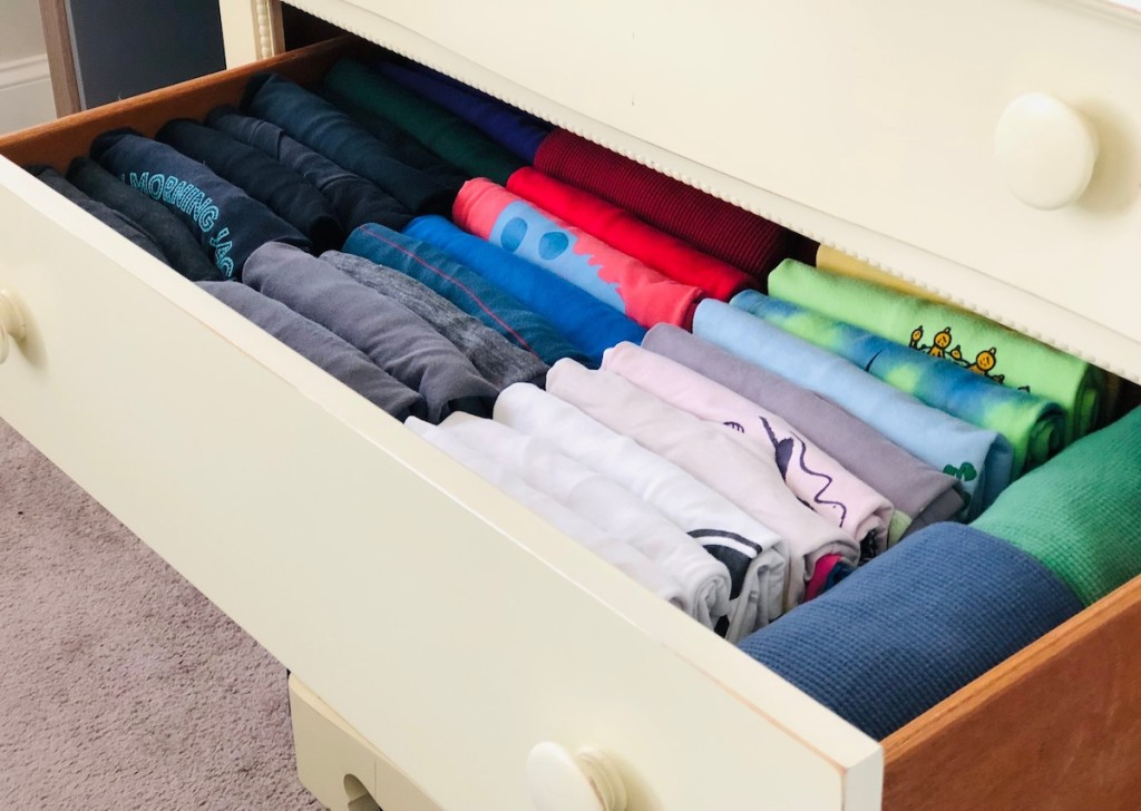 cream colored dress drawer open with various color coordinated shirts