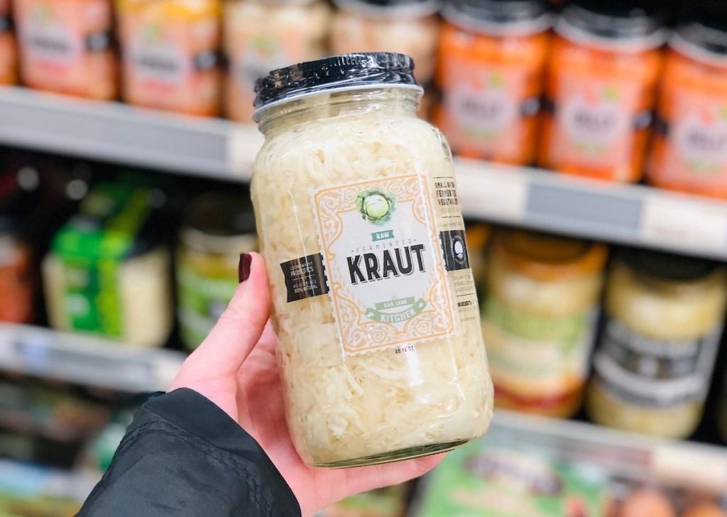 hand holding a glass jar of kraut in store fridge aisle