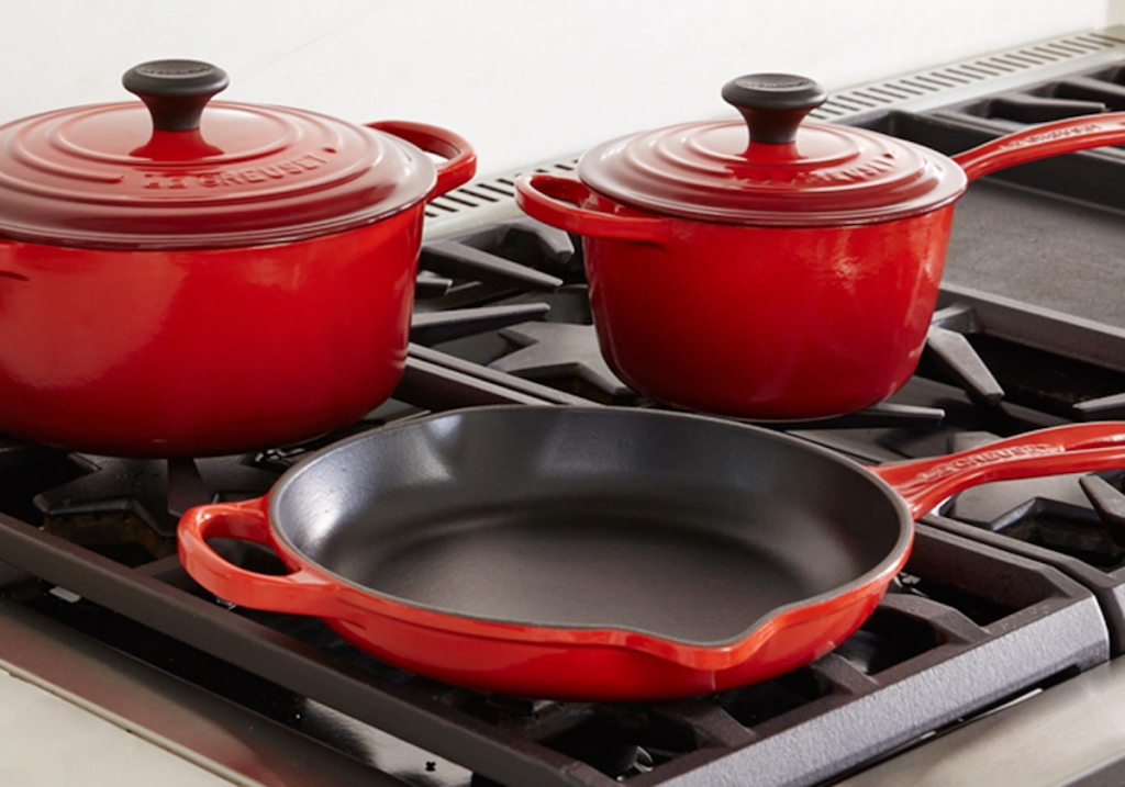 red pots and pans with lids on gar stovetop