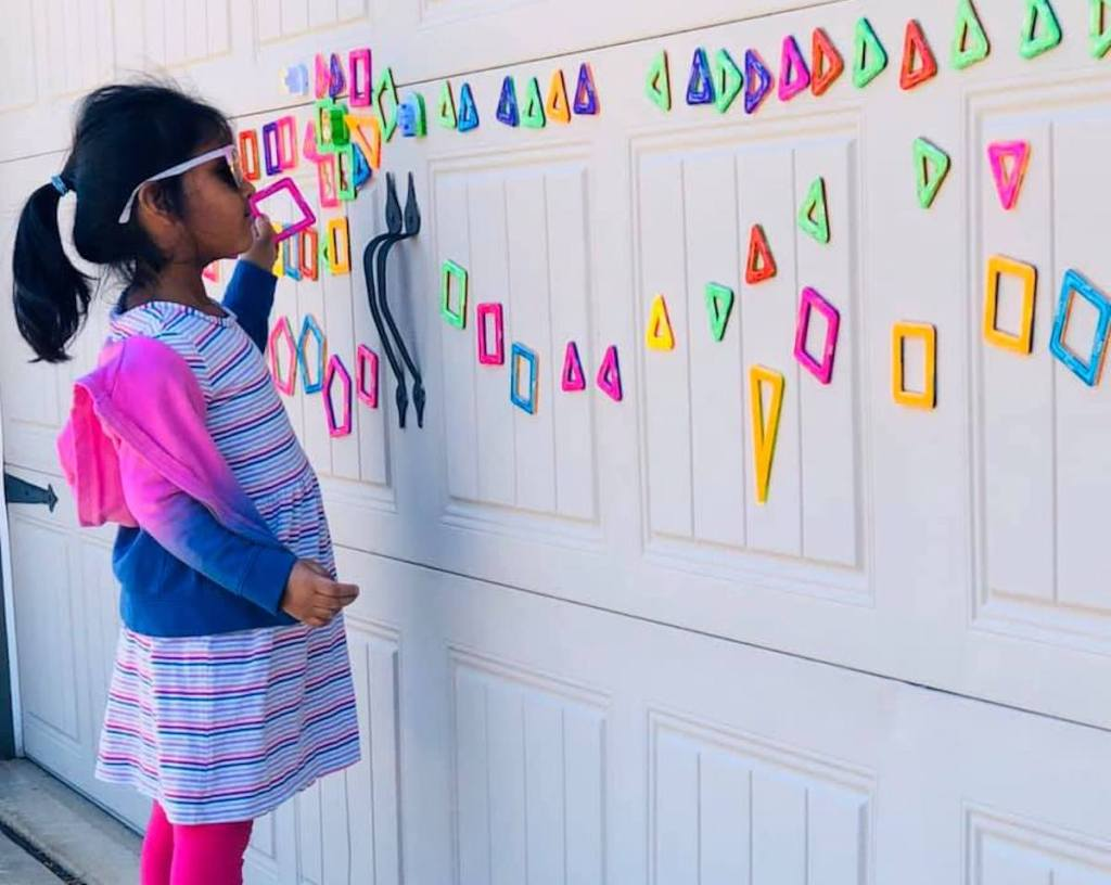 girl standing in front of garage with colorful magnets