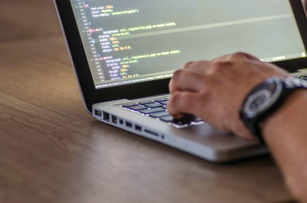 man coding on laptop