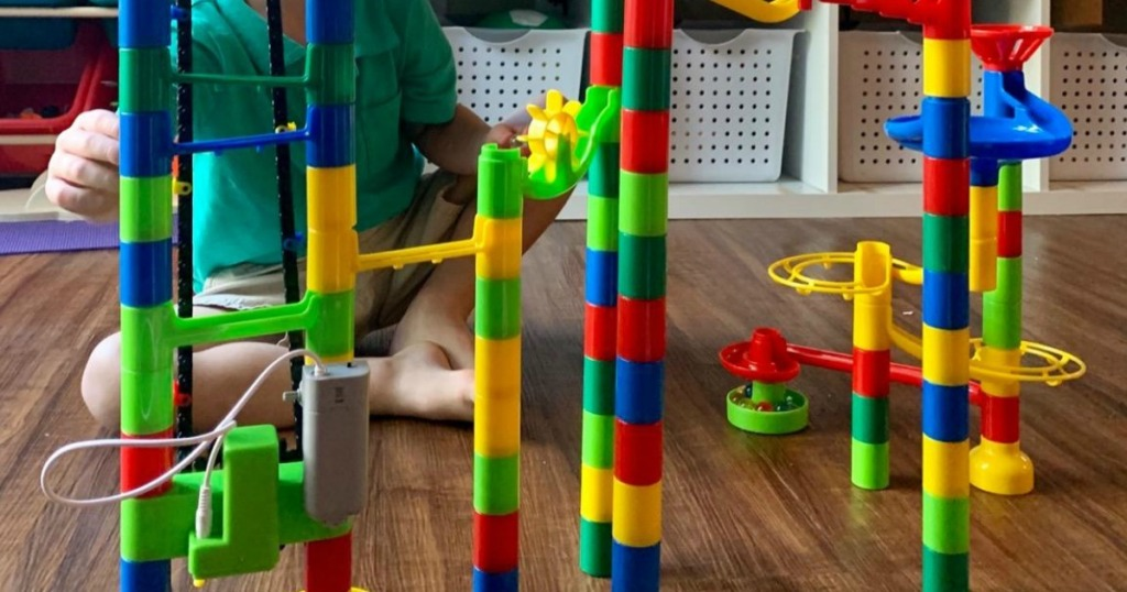 little boy playing with marble run