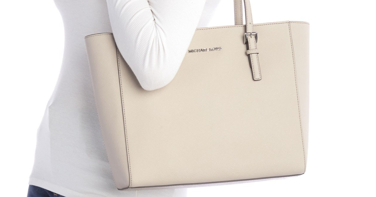 woman wearing white shirt carrying cement colored michael kors tote bag