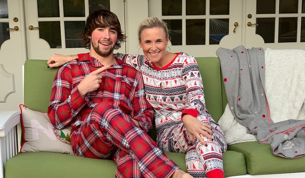 mom and son sitting on porch swing wearing Christmas pajamas