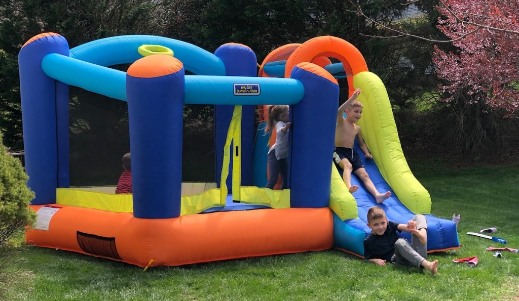 kids jumping on colorful moon bounce outside in yard