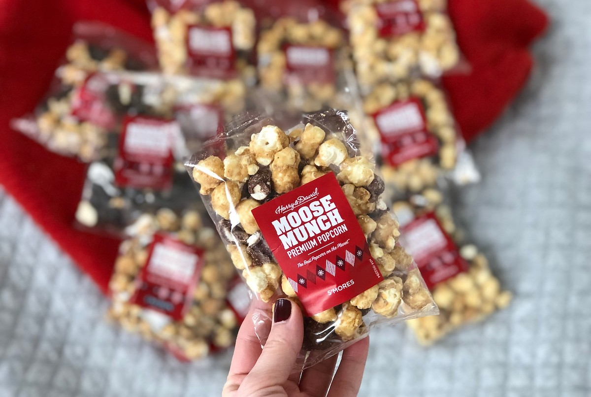 hand holding gifts under 10, moose munch pack of popcorn with various flavors on red blanket in background