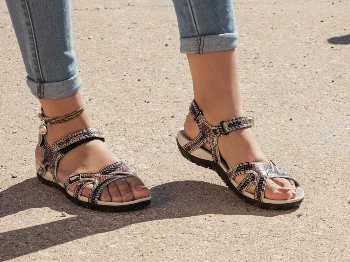 woman's feel wearing muk luks sandals outside with jeans on