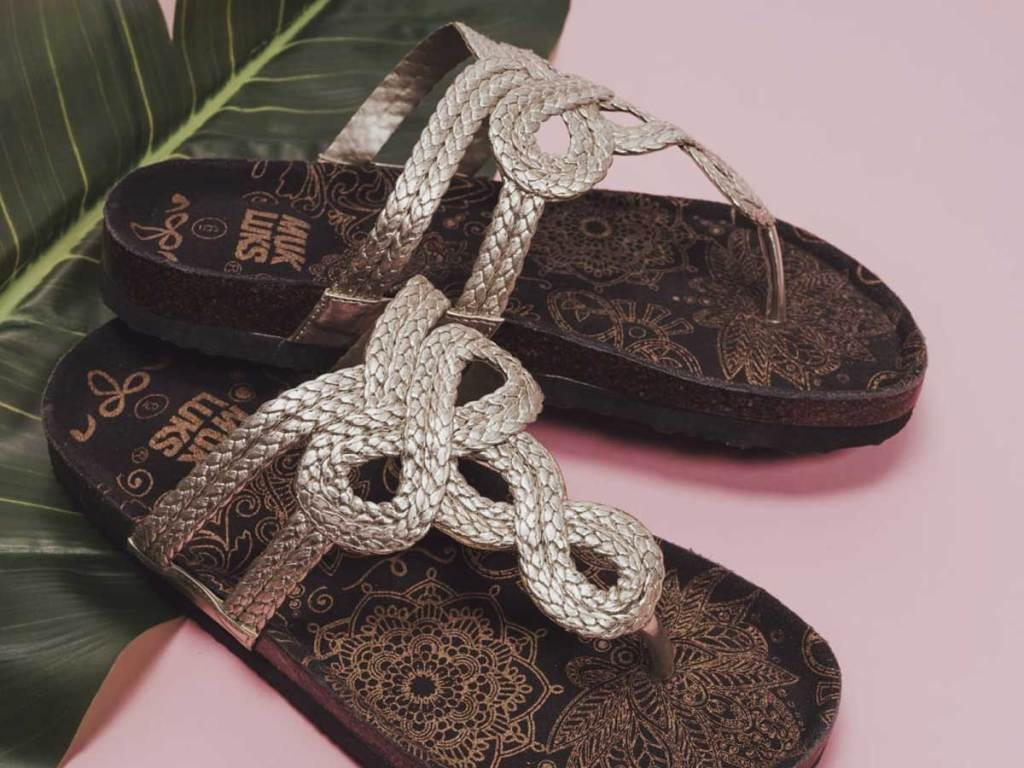 close up picture of muk luks sandals on a palm tree leaf