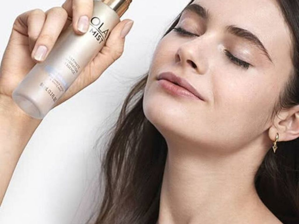 woman spraying olay calming mist on her face