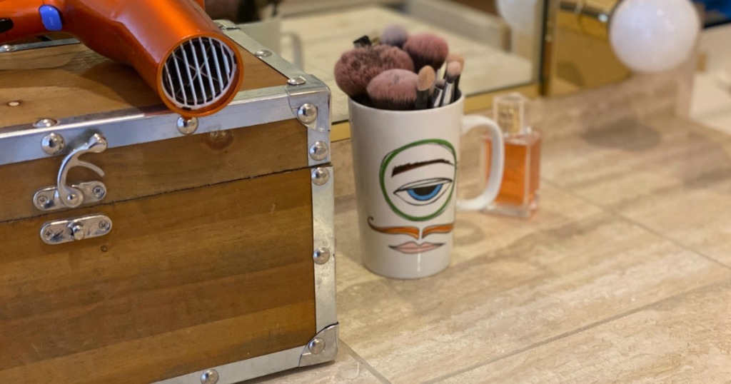 bathroom counter with mug with makeup brushes and storage chest