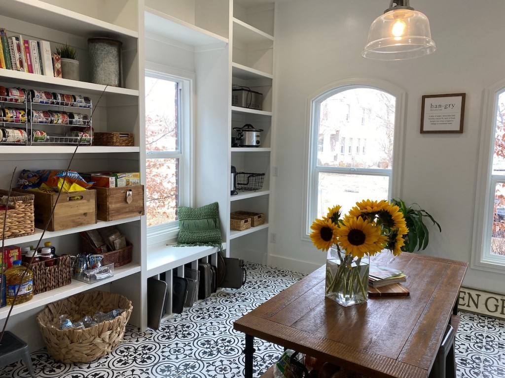 Beautiful organized white pantry room with baskets and table in middle of floor with flowers