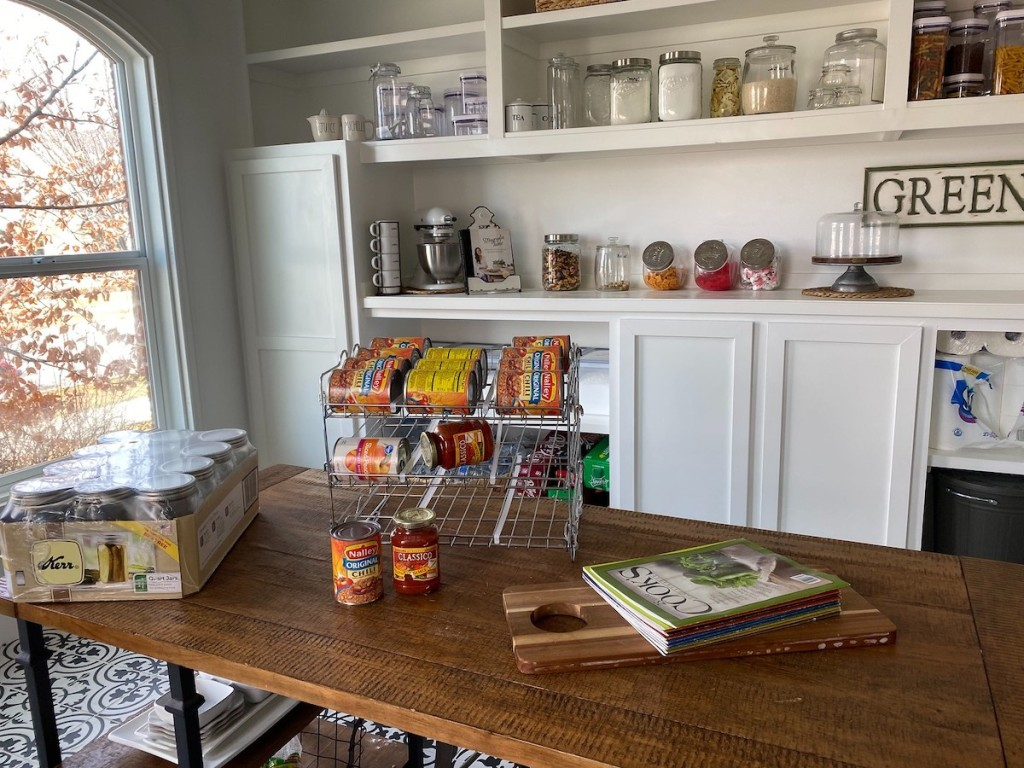 can organizer sitting on wood table in huge pantry room