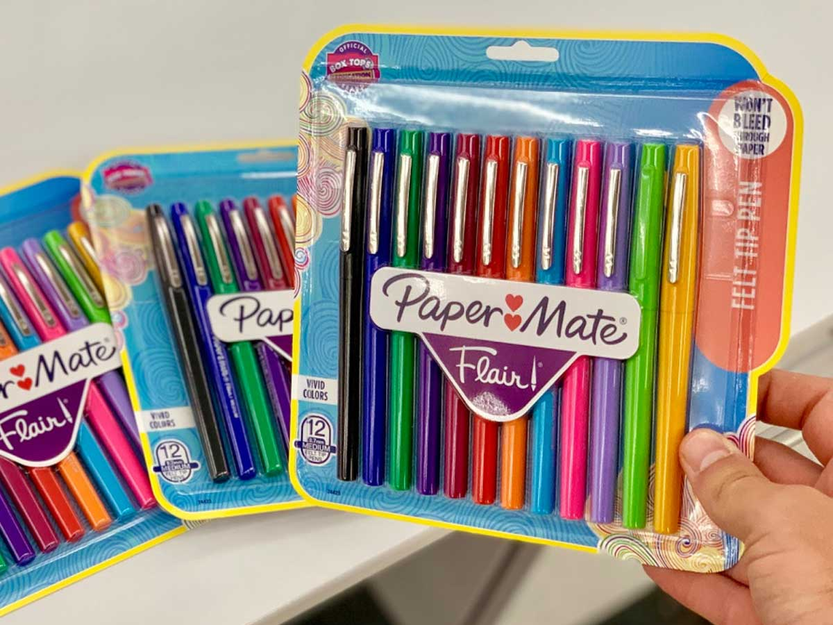 hand holding a paper mate package of markers with 2 packs on a table behind him
