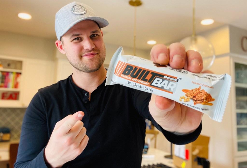 man with peanut caramel built bar
