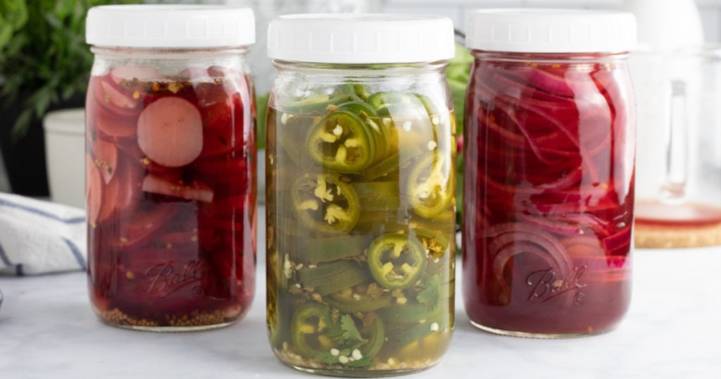 three clear jars with white lids with pickled red and green foods inside