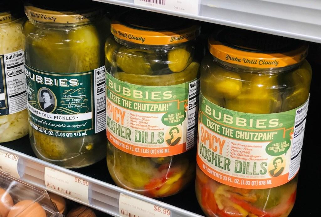 row of pickle jars on store fridge aisle