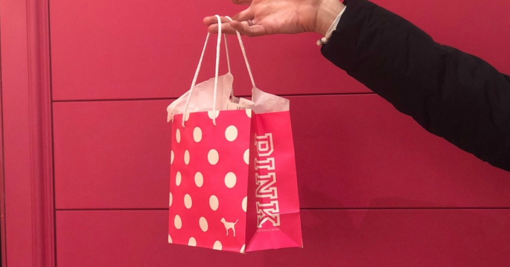 hand holding pink shopping bag
