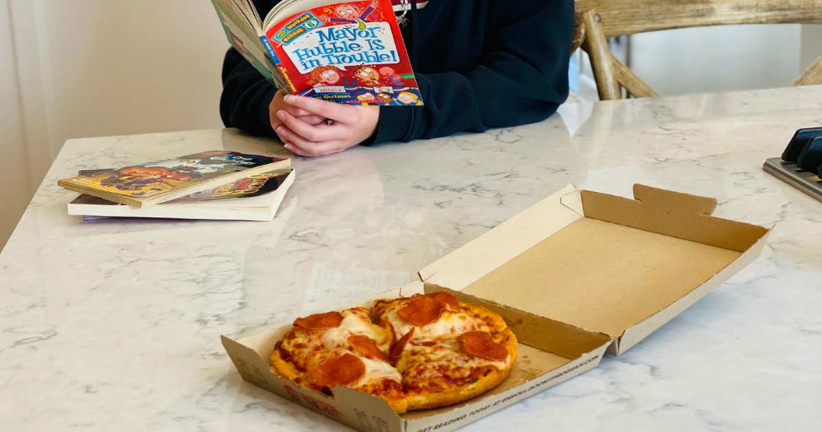 reading book with personal pan pizza on kitchen counter