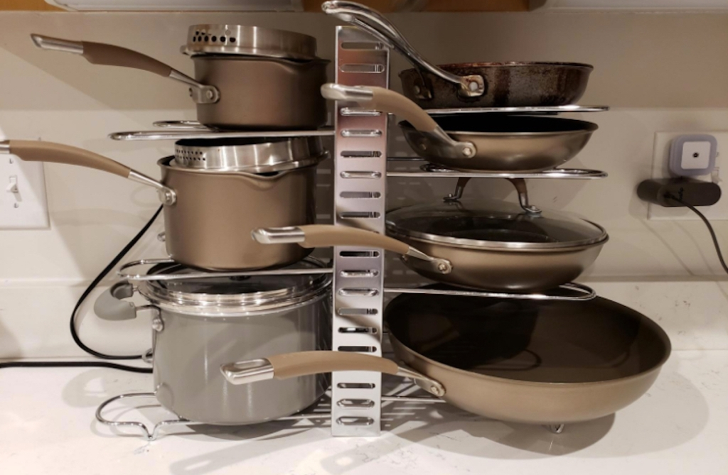organized pots and pans with lids stacked on metal organizer