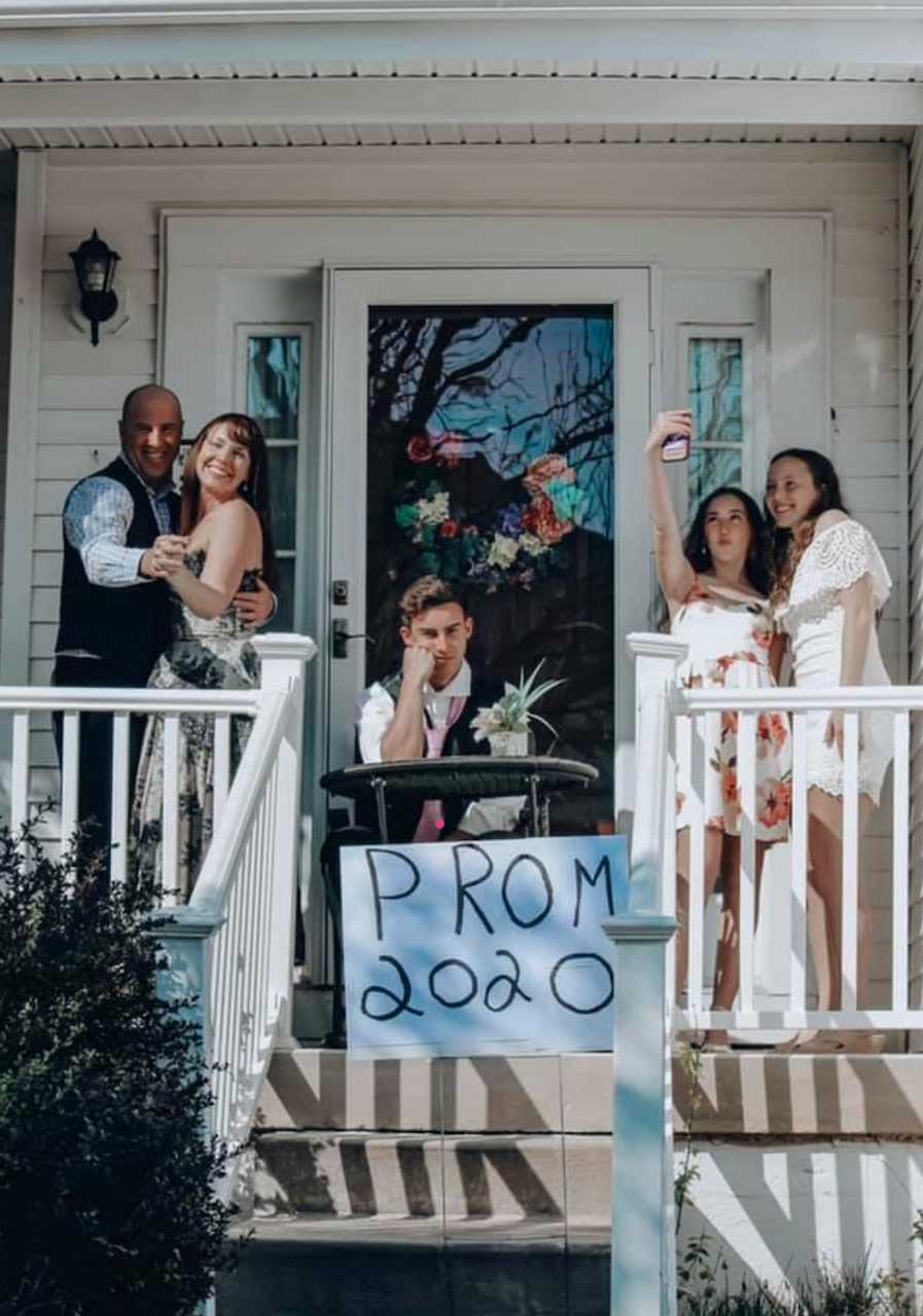 people on front porch dressed up with promo 2020 sign