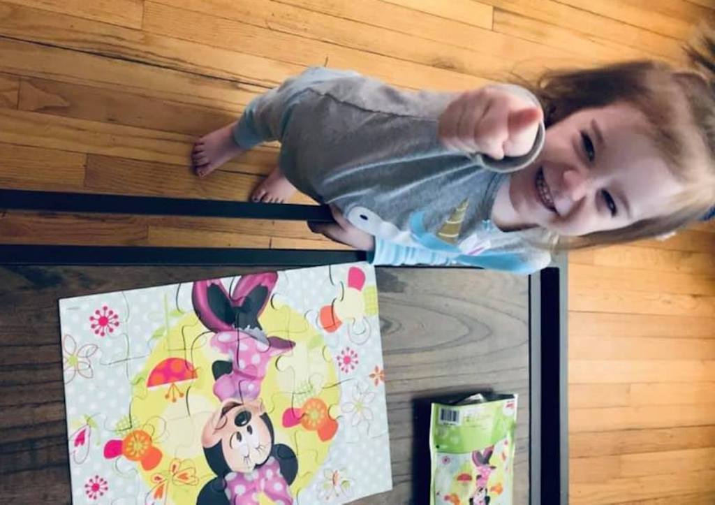 toddler girl pointing and smiling next to minnie mouse puzzle