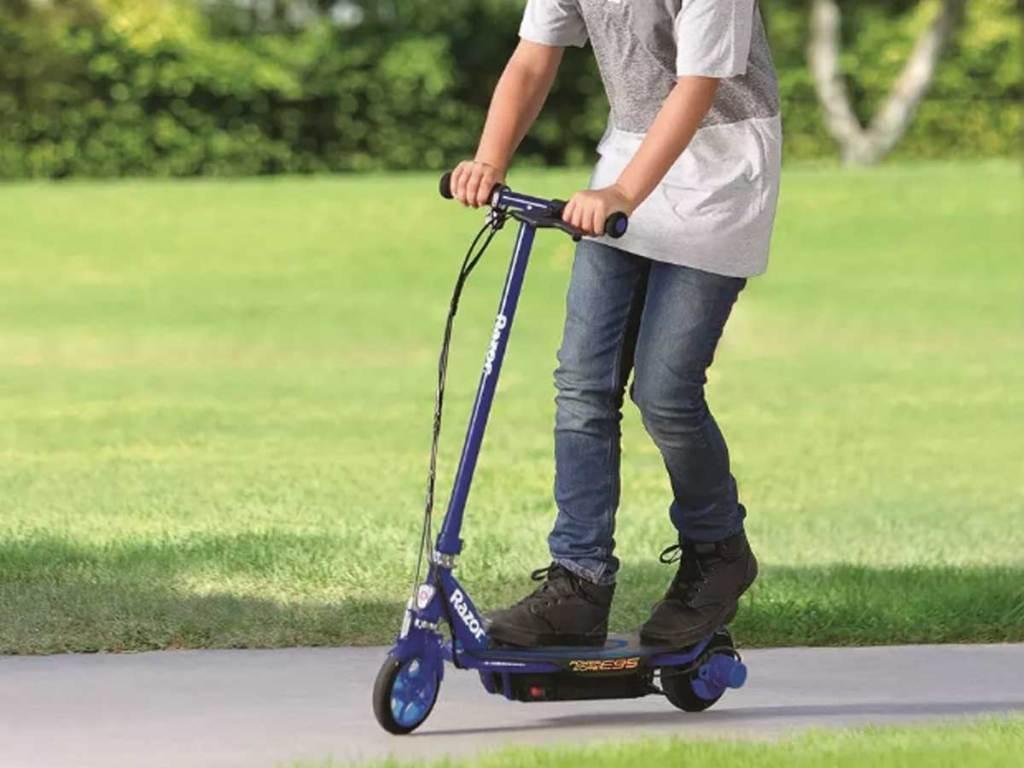 boy riding a blue electric scooter through a park