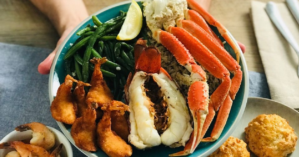 hand holding plate of lobster, green beans and crab legs