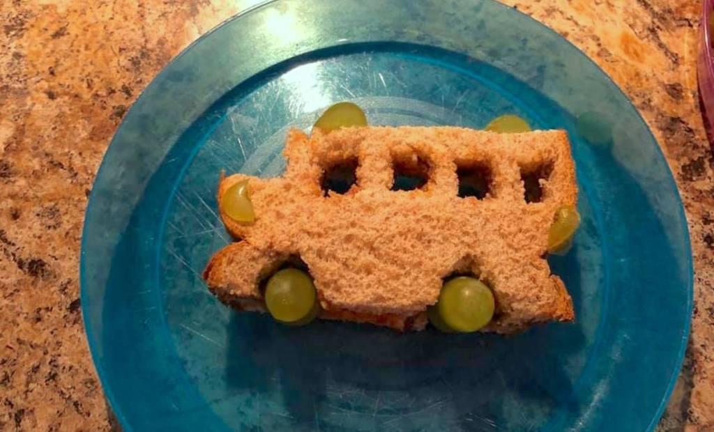 sandwich shaped like a school bus sitting on blue plate